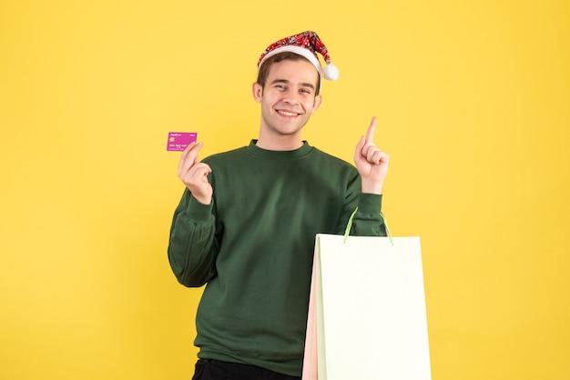 Jovem com chapéu de papai noel segurando sacolas de compras e cartão em pé no espaço de cópia com fundo amarelo