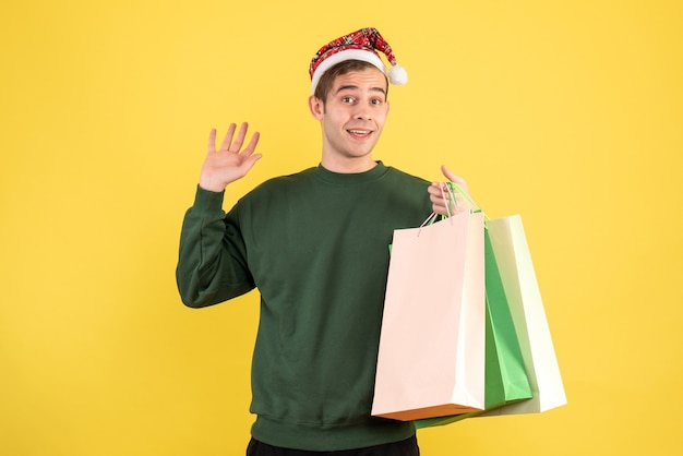 Jovem com chapéu de papai noel segurando sacolas de compras em pé sobre fundo amarelo