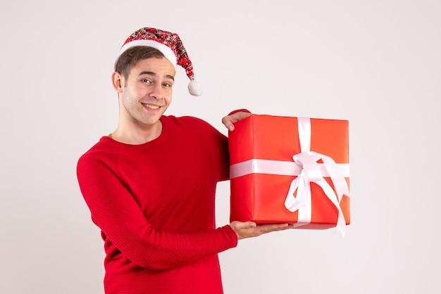 Jovem com chapéu de papai noel segurando uma caixa vermelha de presente em fundo branco