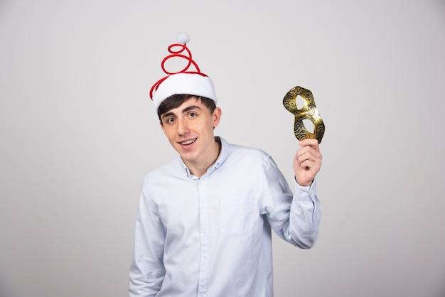 Jovem com chapéu de papai noel segurando uma máscara dourada na parede cinza.