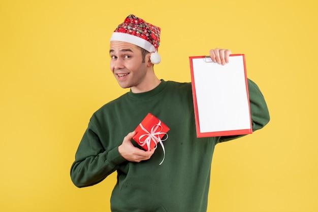 Jovem com chapéu de papai noel segurando uma prancheta e um presente em pé sobre fundo amarelo