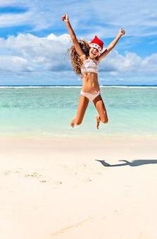 Jovem com chapéu de papai noel vermelho pulando em uma praia tropical