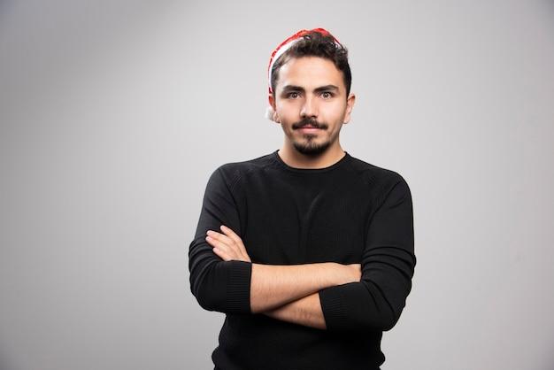 Jovem com chapéu vermelho de papai noel em pé sobre uma parede cinza.