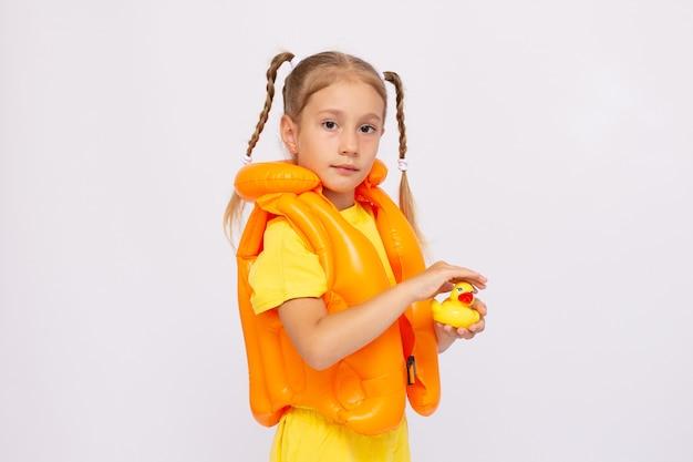 Jovem com colete salva-vidas amarelo e pato de borracha em um fundo branco.