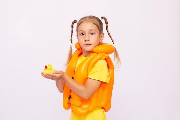Jovem com colete salva-vidas amarelo e um pato de borracha em um fundo branco.