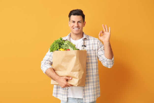 Jovem com comida na sacola mostrando gesto de ok na cor