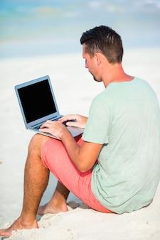 Jovem com computador tablet durante férias de praia tropical
