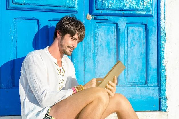 Jovem com computador tablet sorrindo, sentado perto da porta azul, trabalhando no tempo de férias