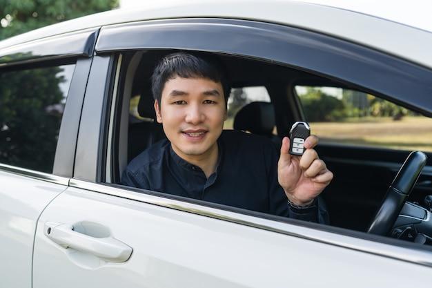 Jovem com controle remoto com chave inteligente em um carro