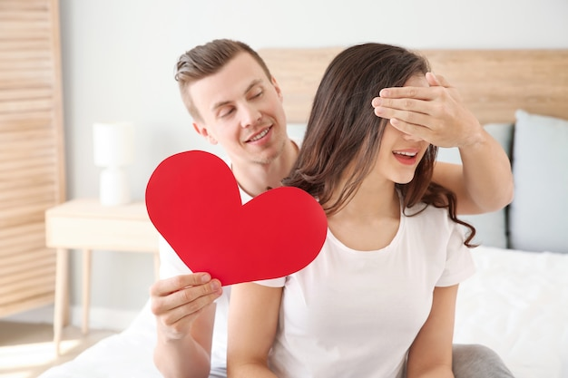 Jovem com coração de papel cobrindo os olhos de sua esposa em casa