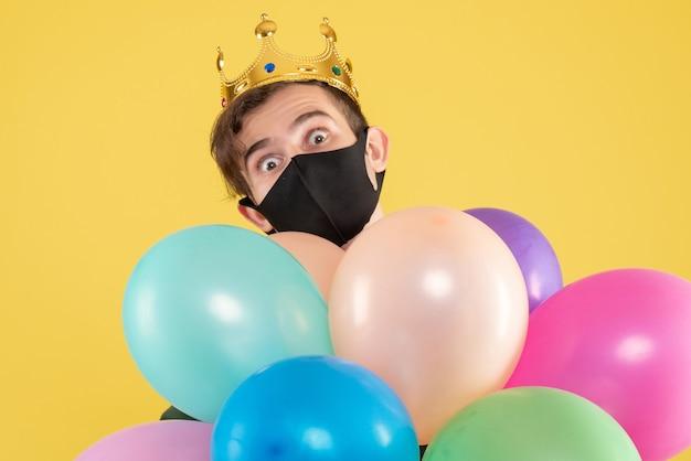 Jovem com coroa e máscara preta segurando balões em amarelo