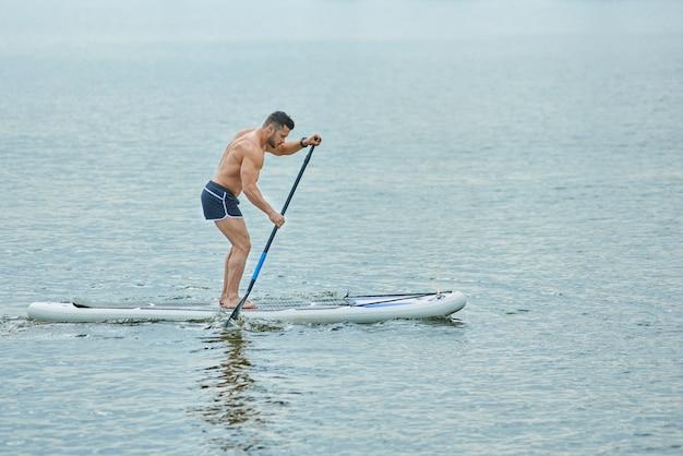 Jovem com corpo desportivo em pé a bordo do sup, roaming com uma poça.