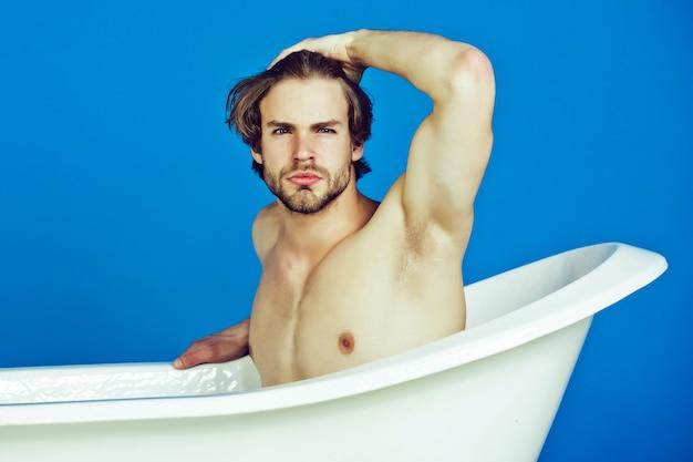 Jovem com corpo musculoso sentado na banheira, beleza, homem sexy, relaxamento e higiene, saúde, cópia espaço