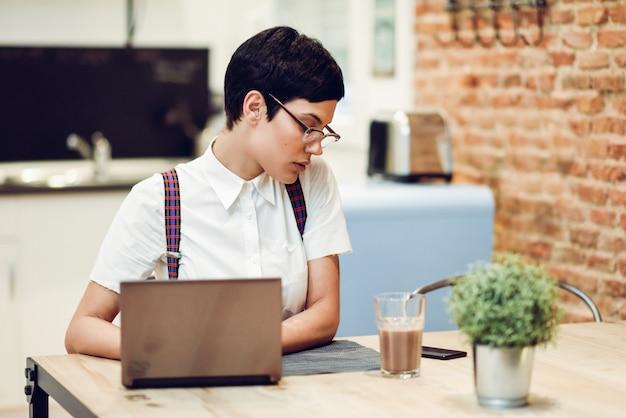 Jovem com corte de cabelo muito curto digitando com um laptop em casa. conceito de trabalho em casa.