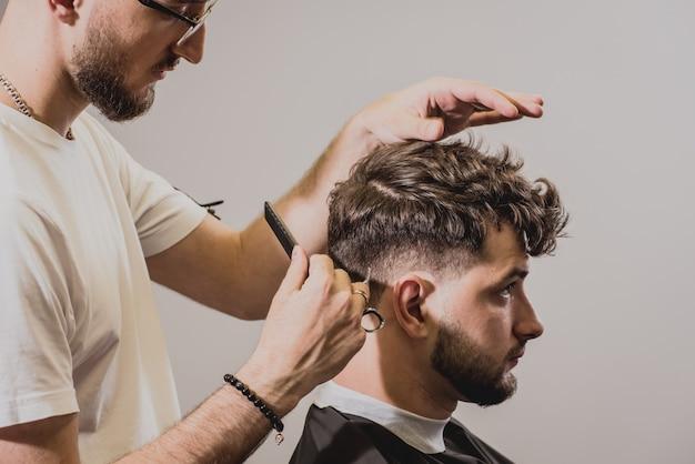 Jovem com corte de cabelo na moda na barbearia. o barbeiro faz o penteado e a barba.
