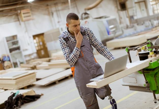 Jovem com deficiência com uma perna artificial está trabalhando na fábrica de móveis