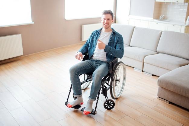 Jovem com deficiência, sentado na cadeira de rodas. sozinho na grande sala vazia. segurando o polegar grande e sorrir.