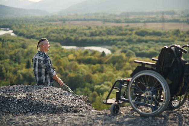 Jovem com deficiência sentado no topo da montanha perto de cadeira de rodas e apreciando o ar fresco e a beleza da natureza. aproveitando a vida.