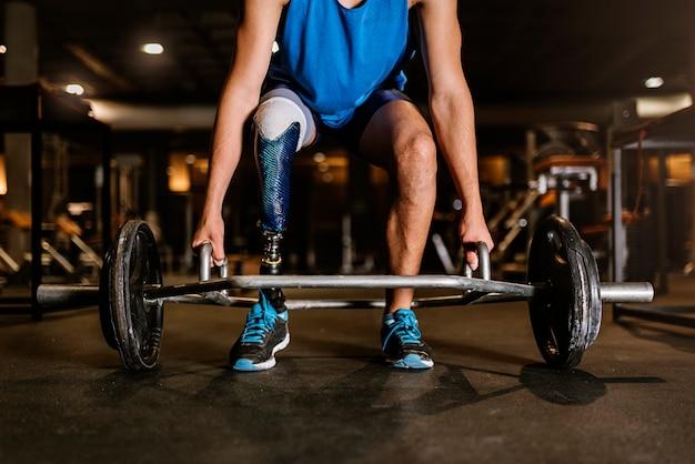 Jovem com deficiência treinando no ginásio. conceito de desportista com deficiência.