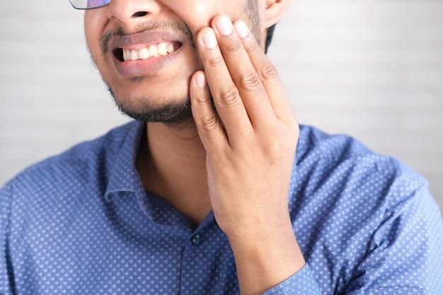 Jovem com dentes sensíveis close-up