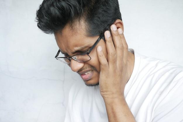 Jovem com dor de ouvido tocando sua orelha dolorida
