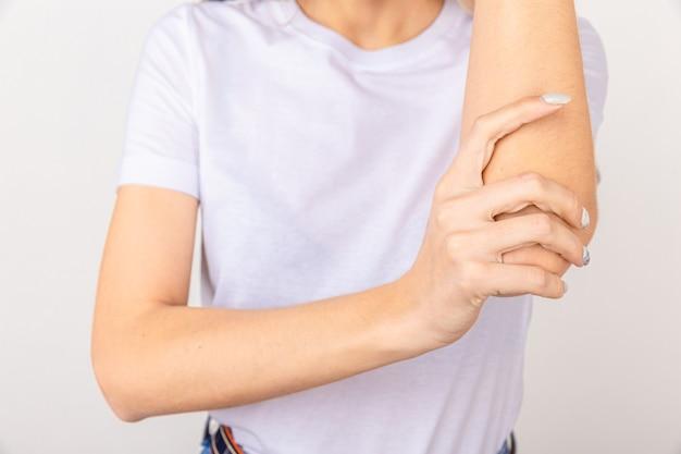 Jovem com dor no cotovelo, inflamação das articulações, isolada no fundo branco.