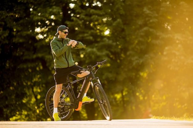 Jovem com ebike, bicicleta de montanha com bateria elétrica, verificando o tempo no parque