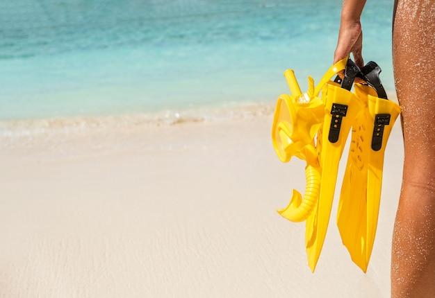 Jovem com equipamento de mergulho amarelo em pé à beira-mar. férias de verão e conceito de viagens