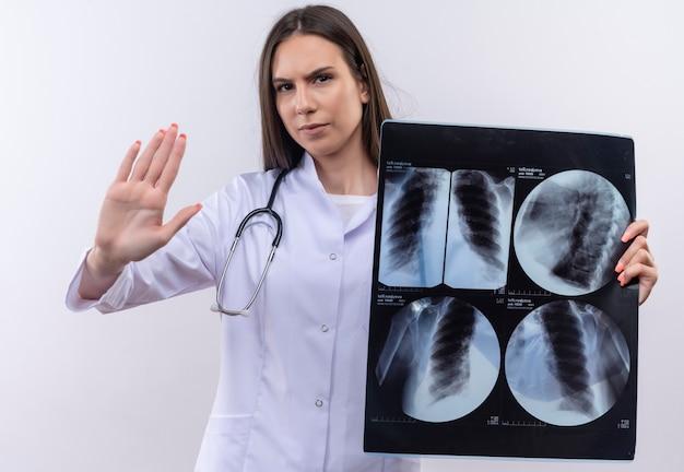Jovem com estetoscópio vestido de médico segurando um raio-x mostrando gesto de parada na parede branca