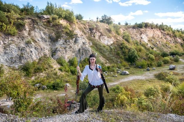 Jovem com estilo indígena americano segurando arco e flecha na natureza