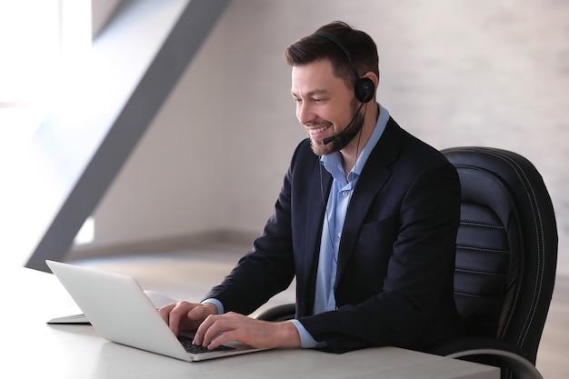 Jovem com fone de ouvido e laptop trabalhando no escritório