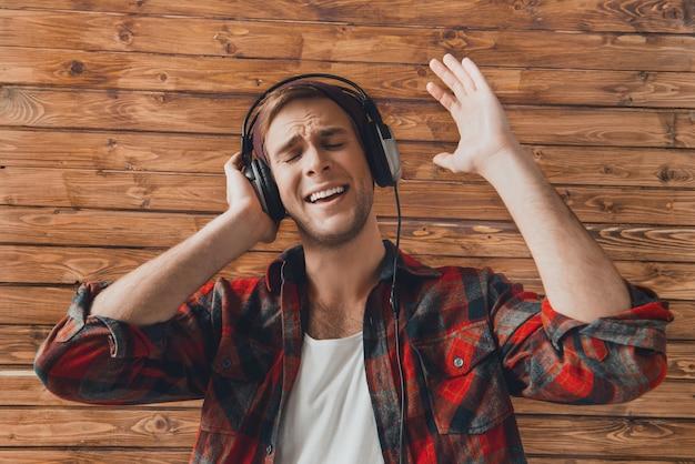 Jovem com fones de ouvido cantando na parede de madeira