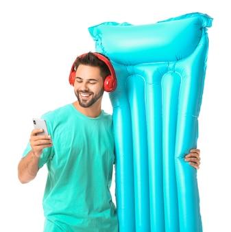 Jovem com fones de ouvido, colchão inflável e celular na superfície branca