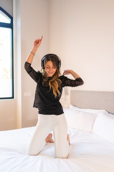 Jovem com fones de ouvido curtindo música em cima da cama