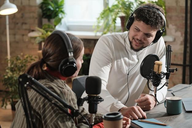 Jovem com fones de ouvido falando no microfone e conversando com seu colega durante uma transmissão no estúdio de rádio