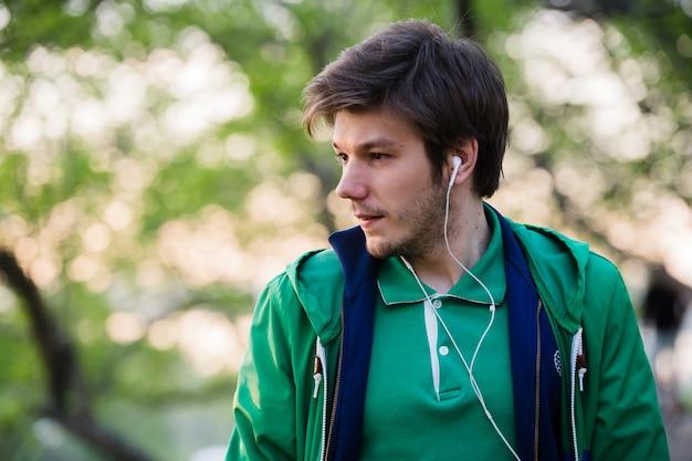 Jovem com fones de ouvido ouvindo música. retrato de pessoa no parque, que está pensando em alguma coisa.