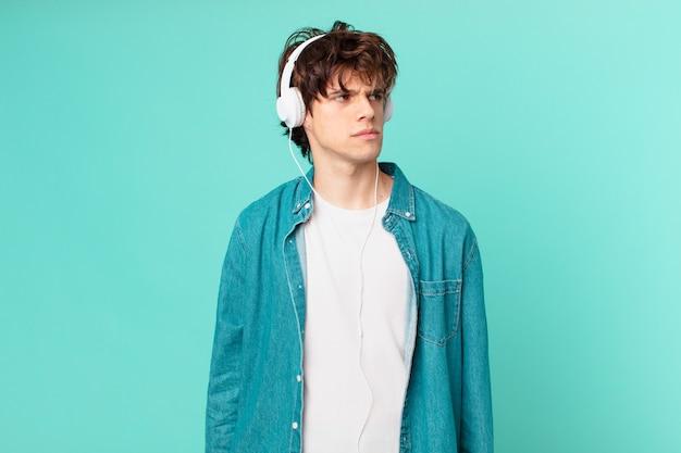 Jovem com fones de ouvido, sentindo-se triste, chateado ou com raiva e olhando para o lado