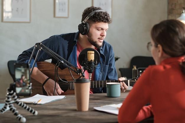 Jovem com fones de ouvido, tocando guitarra e se apresentando no rádio com o dj de rádio sentado à sua frente