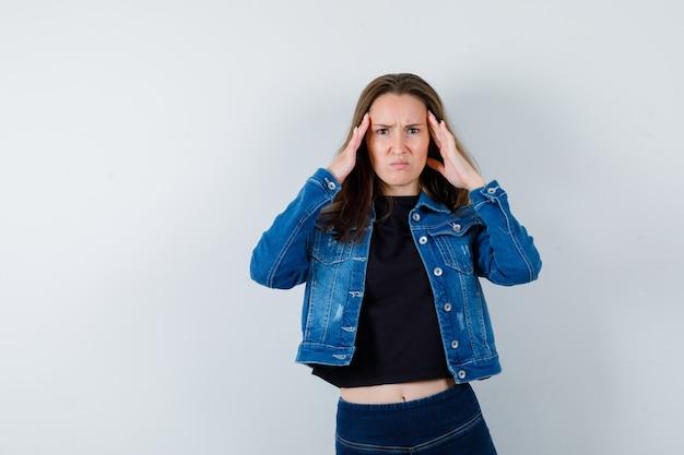 Jovem com forte dor de cabeça na blusa, jaqueta e parecendo chateada