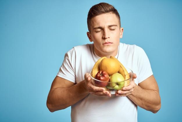 Jovem com frutas nas mãos, dieta de frutas