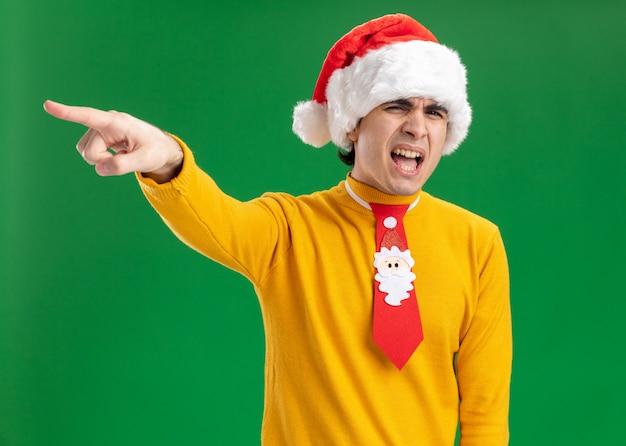 Jovem com gola alta amarela e chapéu de papai noel com gravata engraçada gritando com expressão irritada apontando com o dedo indicador para algo em pé sobre a parede verde