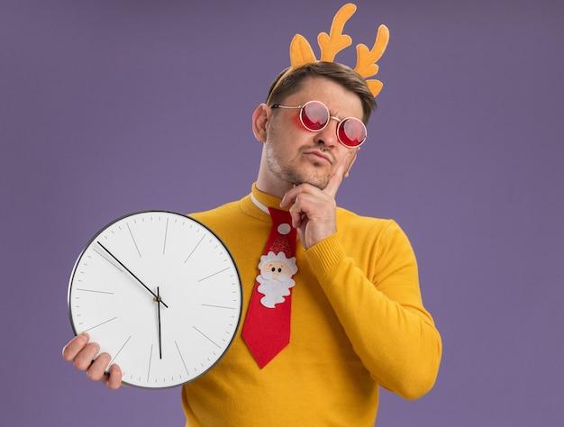 Jovem com gola alta amarela e óculos vermelhos, usando gravata vermelha engraçada e aro com chifres de veado na cabeça, segurando um relógio de parede, olhando de lado perplexo em pé sobre um fundo roxo