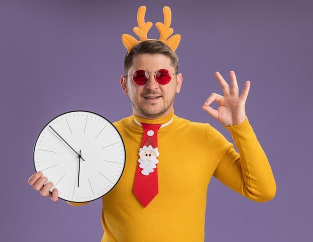 Jovem com gola amarela e óculos vermelhos, usando gravata vermelha engraçada e aro com chifres de veado na cabeça, segurando um relógio de parede, olhando para a câmera, sorrindo, mostrando uma placa de ok em pé sobre um fundo roxo