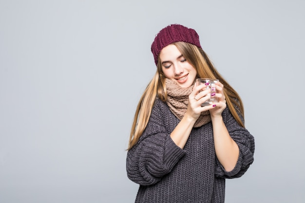 Jovem com gripe e bebidas geladas, bebida quente, chá de ervas para ficar saudável em cinza