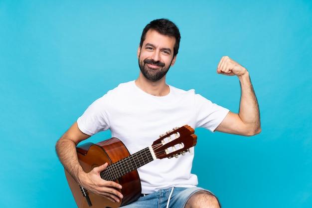 Jovem com guitarra fazendo gesto forte