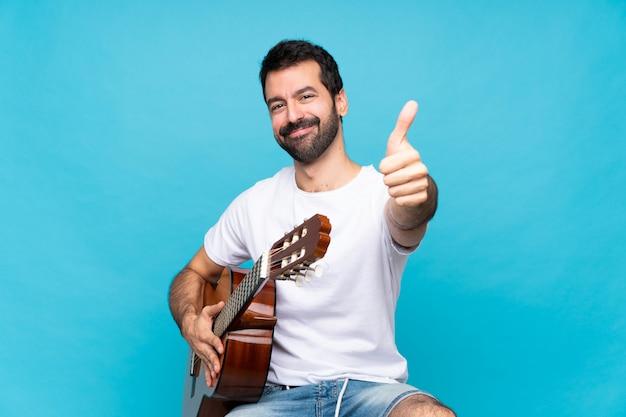 Jovem com guitarra isolado azul com polegares para cima porque algo bom aconteceu
