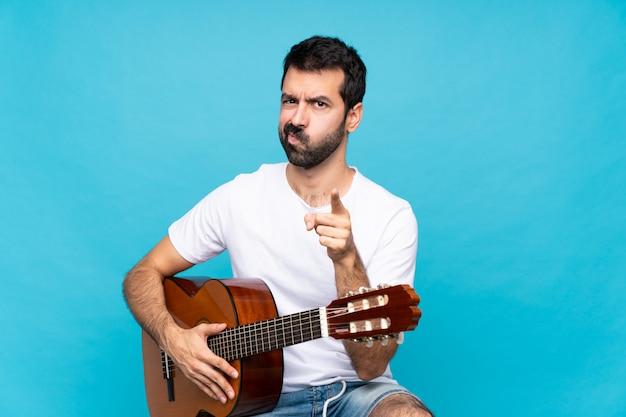 Jovem com guitarra isolado azul frustrado e apontando para a frente