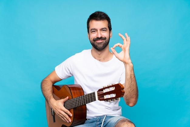 Jovem com guitarra isolado azul mostrando sinal de ok com os dedos