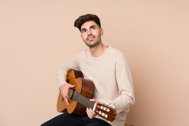 Jovem com guitarra, olhando para cima enquanto sorrindo