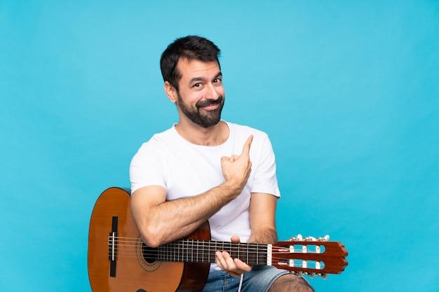 Jovem com guitarra sobre azul isolado apontando para trás